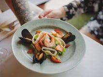 Конец-вверх плиты с морепродуктами, обслуживания обедающего и бокала вина в руке ` s кельнера на белой скатерти Стоковые Изображения