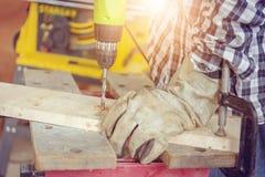 Конец вверх плотника использует сверло к отверстию mae в деревянном p стоковые изображения