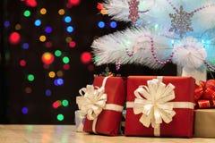 Конец-вверх подарков под украшенной рождественской елкой против bac Стоковые Изображения