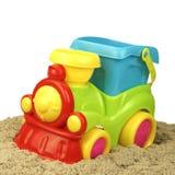 Конец-вверх поезда игрушки при изолированная куча песка Стоковая Фотография