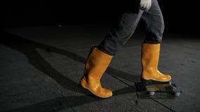 Конец-вверх положения человека в масштабах Конец-вверх ног работника в джинсах и резиновые ботинки стоят в масштабах лежа на серо сток-видео