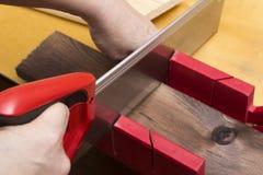Конец вверх построителей с рукой увидел доску sawing Стоковое Фото