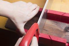 Конец вверх построителей с рукой увидел доску sawing Стоковая Фотография