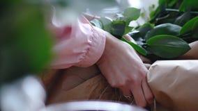 Конец вверх по взгляду: руки ` s флориста связывают современный букет стоковые изображения