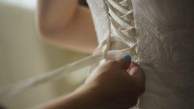 Конец вверх по взгляду женщины затягивает корсет платья свадьбы сток-видео