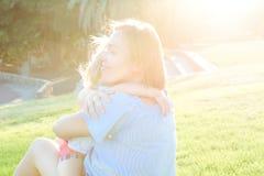 Конец вверх по дочери младенца матери и малыша ослабляя, обнимающ, смеющся над и имеет потеху на луге зеленой травы на заходе сол Стоковая Фотография RF