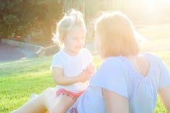 Конец вверх по дочери младенца матери и малыша ослабляя, обнимающ, смеющся над и имеет потеху на луге зеленой травы на заходе сол Стоковая Фотография