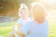 Конец вверх по дочери младенца матери и малыша ослабляя, обнимающ, смеющся над и имеет потеху на луге зеленой травы на заходе сол Стоковое фото RF