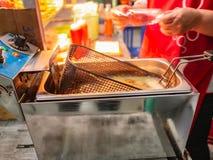 Конец вверх по жарить машину жаря сосиску стоковые фото