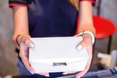 Конец вверх по женским рукам держа и давая принимает вне еду в коробке белой бумаги через окно выдавать заказы Селективный фокус  стоковое фото rf