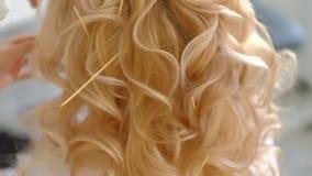 Конец вверх по женским рукам сделать светлые волосы волос длиной длинные волнистые стиль причесок снятый в замедленном движении сток-видео