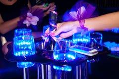 Конец вверх по женской руке достигает для бутылки шампанского на партии ночи куриц-партийный перед свадьбой Стоковые Изображения RF