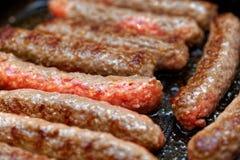 Конец вверх по зажаренным домодельным сосискам мяса Малая глубина поле стоковое фото