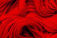 Конец вверх по красному потоку пряжи как абстрактная предпосылка стоковая фотография