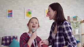 Конец вверх по маме и дочь эмоционально поют караоке дома сток-видео