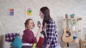 Конец вверх по маме и дочь эмоционально поют караоке дома медленный mo сток-видео