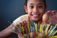 Конец вверх по милой азиатской девушке усмехаясь и держа яйцо цыпленка стоковая фотография rf