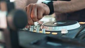 Конец вверх по мужским рукам DJ играя комплект музыки смешивая и царапая на профессиональном оборудовании музыки видеоматериал