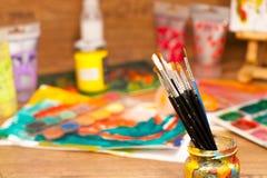 Конец вверх по натюрморту чистит краски щеткой поставек искусства для красить и рисовать Стоковые Изображения