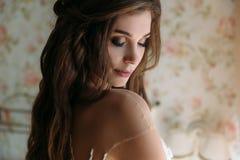 Конец вверх по портрету красивой невесты понизил ее глаза вниз, показывает состав в белых стойках платья свадьбы в ее комнате вну Стоковые Изображения RF