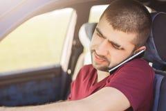 Конец вверх по портрету сфокусированного небритого мужского водителя говорит через сотовый телефон пока приводы автомобиль, наход стоковые изображения rf