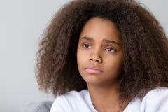 Конец вверх по расстроенному внимательному Афро-американскому девочка-подростку сидя самостоятельно стоковые фотографии rf