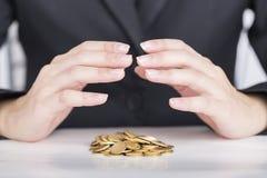 Конец вверх по рукам дела сохраняет деньги к стогу монеток стоковое изображение rf