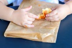 Конец вверх по рукам ребенк держа круассан стоковое изображение