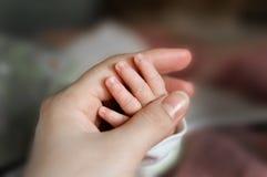 Конец вверх по руке младенца положил на руку мамы Младенец ухода мамы мама и ребенок ослабляют дома Интерьер питомника Feedin гру стоковые изображения
