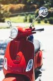Конец вверх по скутеру красного цвета винтажному в улице лета города, мотоцикле хипстера на городской предпосылке, велосипеде пер стоковое изображение