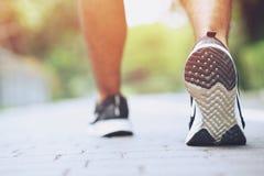 Конец вверх по спортсмену бегуна людей фитнеса ботинка бежать на на дороге стоковое фото