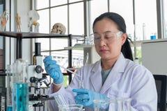 Конец вверх по съемке, ученым среднего возраста азиатским женским в лаборатории специалист, работает пробирка для того чтобы сдел стоковое изображение