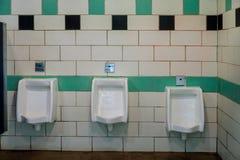 Конец вверх по туалету белых людей писсуаров общественному в керамических писсуарах в комнате туалета стоковое фото rf