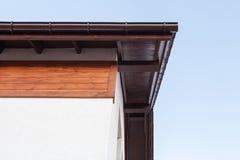 Конец вверх по фото взгляда сверху низкого угла коричневого угла крыши с деревянными элементами поверх небольшого удобного дома с стоковые изображения
