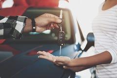 Конец вверх по человеку дает ключи к женщине Афро-американская семья на автосалоне Отец, мать и сын около нового автомобиля стоковое фото