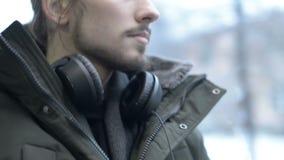 Конец вверх по человеку портрета молодому длинному с волосами бородатому в куртке и больших наушниках сидит публично переход трам сток-видео