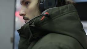 Конец вверх по человеку портрета молодому длинному с волосами бородатому в куртке и больших наушниках сидит публично переход трам видеоматериал