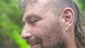 Конец вверх по человеку стороны красивому бородатому смотря к камере и усмехаться Человек портрета взрослый с bristly стороной сток-видео