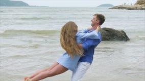 Конец вверх по человеку объезжает девушку в его оружиях на песчаном пляже моря Пара свирли любовников в замедленном движении видеоматериал
