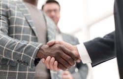 конец вверх предприниматели рукопожатия на предпосылке офиса стоковое изображение rf