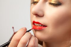 Конец-вверх применяясь на губах, художник макияжа держит щетку в ее руке и прикладывает красную губную помаду на рте модели откры стоковые фото