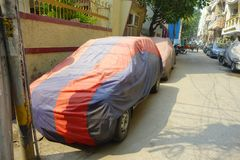 Конец вверх припаркованного автомобиля покрытый с огромной тканью с цветом красным и синью, около виска Laxminarayan, a Стоковые Фото