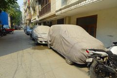 Конец вверх припаркованного автомобиля покрытый с огромной тканью с цветом красным и синью, около виска Laxminarayan, a Стоковое Фото
