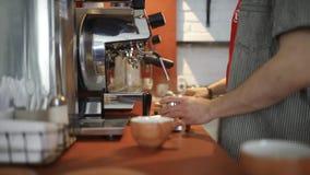 Конец-вверх профессионального barista льет кофе от машины кофе r Овладение в управлении оборудования кофе и акции видеоматериалы