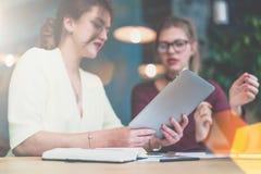 Конец-вверх планшета в руках молодой коммерсантки сидя на таблице Стоковое Изображение RF