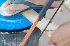 Конец вверх плотника пиля доску с древесиной руки увидел Стоковое Изображение RF