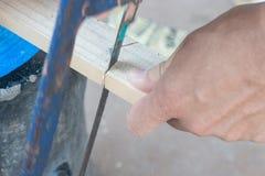 Конец вверх плотника пиля доску с древесиной руки увидел Стоковые Изображения