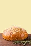 Конец-вверх плюшки бургера с семенами сезама на желтой предпосылке Стоковое фото RF