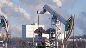 Конец-вверх работая насоса для извлечения сырой нефти и ` s нефтехимического завода пускает излучения по трубам сток-видео