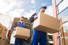 Конец-вверх 2 работников доставляющих покупки на дом нося картонную коробку стоковые фото
